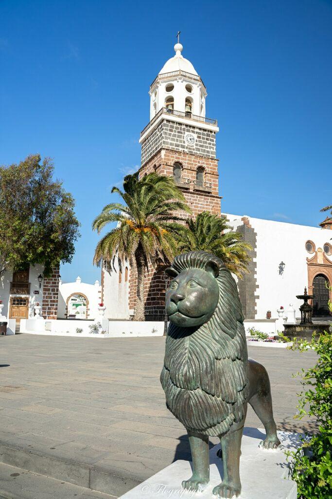 statue de lion et son église avec son clocher dans le village de Teguise à Lanzarote