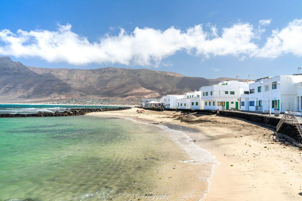 plage de Famara avec des maisons blanches et montagne de volcans de Lanzarote aux canaries