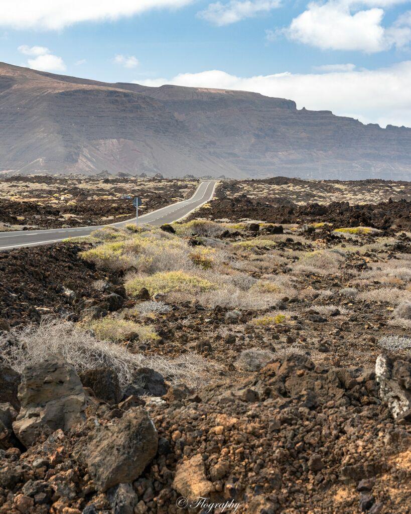 route aride bordée de roches de lave à Lanzarote aux Canaries