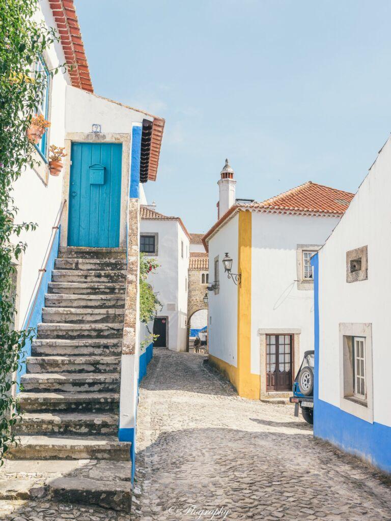 village d'Obidos au Portugal avec des maisons colorées et escalier bleu jaune rue pavés