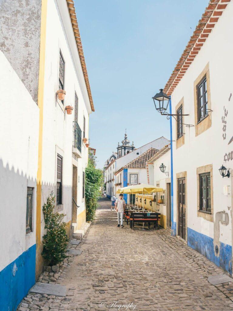 rue d'Obidos au Portugal avec maison jaune et bleu et l'église
